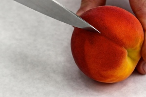 The peach has a 'butt' and you want to cut along its 'crack.' If the peach is really ripe you'll cut the seed in half. If it's a little less ready, you might get the entire seed left in one half. (It's ok to bake the seed too.)