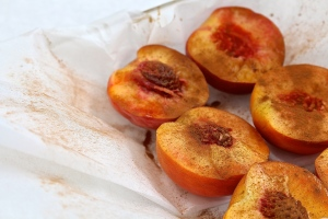 Line baking dish with parchment paper. Expose insides of peach and sprinkle with cinnamon and vanilla. If you do this before your guests arrive they get the gift of a yummy smelling house.