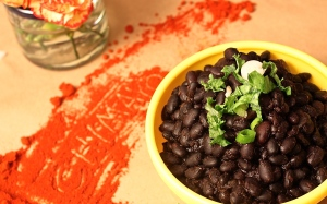 Chimayo Chile powder is vibrant reddish-orange, and adds a subtle sweetness to cooked black beans.