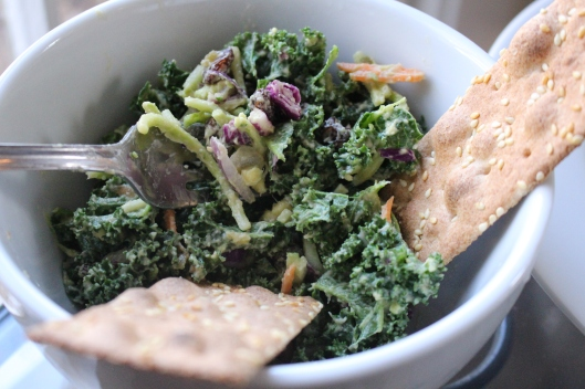 LUNCH -- Kale massaged with hummus / avocado -- purple onion, purple cabbage and carrots sprinkled in. (Raisins too!) Served with ok-mok sesame crackers.
