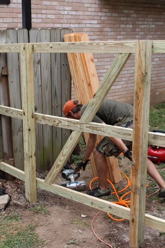 The contractor built the fence like it would have no gate. And at the end simply used a circular saw to cut the rafters to make way for the gate opening. He said most people will build the gate on the ground and will have a really hard time hanging it and lining it up to match the rest of the fence. The way he does it, the gate planks line up perfectly ...if it wasn't for the gate hardware, you wouldn't even know the door was there.