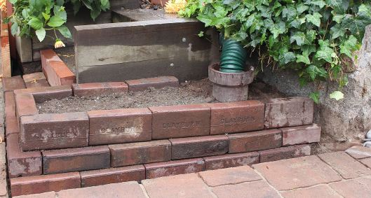 We also rebuilt this brick wall surrounding a drainage pipe. For Leslie, it's a new planting area.